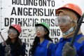 Genta Kalbu Tanjung (left), a 20-year-old student, with her two friends after a session at the Temper Clinic in Jakarta, Indonesia, where they smashed bottles with crowbars as part of their destruction therapy. Photo: AFP