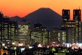 Japan's highest mountain, Mt Fuji, is seen in the background between skyscrapers in Tokyo. Japan is looking to draw 40 million tourists a year. Photo: AFP