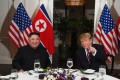 US President Donald Trump (R) speaks with North Korea's leader Kim Jong Un as they sit for a dinner at the Sofitel Legend Metropole hotel in Hanoi on February 27, 2019. (Photo by Saul LOEB / AFP)