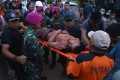Rescue workers carry a miner who survived following the collapse of an illegal gold mine at Bolaang Mongondow. Photo: Reuters