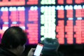 Investors track the movement of shares at a stock trading hall in Shanghai on Monday, a day when major stock indices in China surged more than 5 per cent. Photo: Xinhua