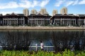 Expensive lakeside villas stand in front of public housing in the Chaoyang district of Beijing. Luxury property sales have been declining in China. Photo: AFP