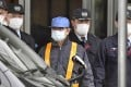 Ghosn (wearing blue cap) leaves the Tokyo Detention House on March 6, 2019. Photo: Reuters.