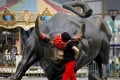 China's markets are on fire. Here, a Chinese woman touches a bull statue on display in Beijing on June 18, 2018. Photo: Associated Press