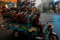 A man rides a tricycle transporting Mobike shared bikes near Wangfujing Street in Beijing on October 15, 2018. Photo: Reuters