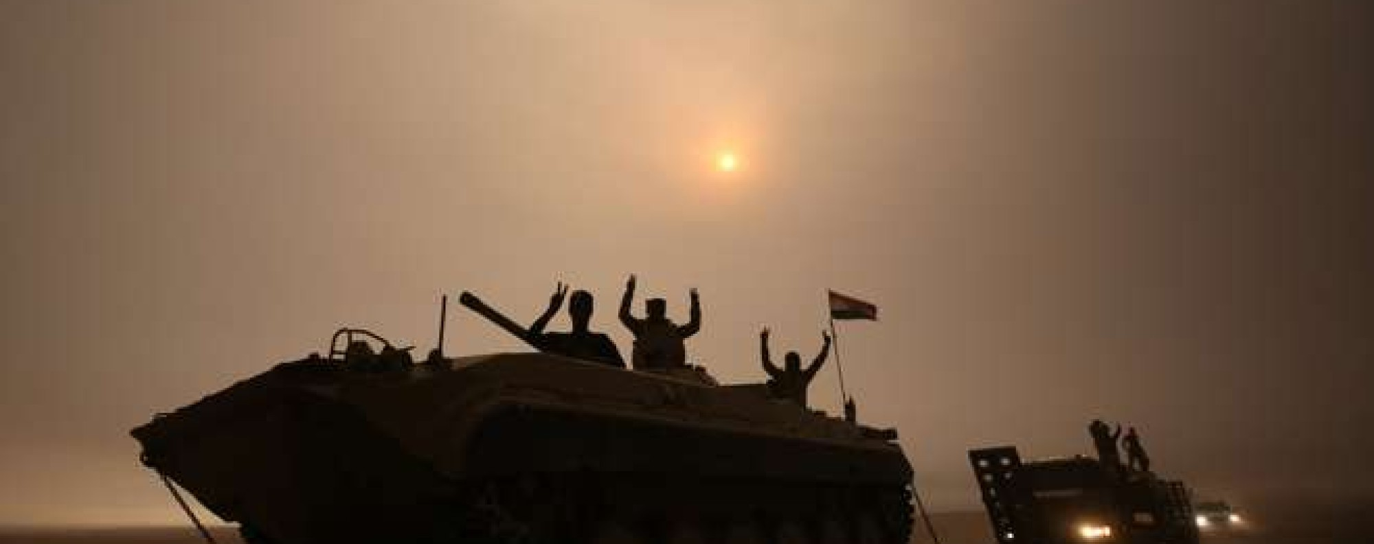 Iraqi forces flash the V-sign as they stand on an infantry fighting vehicle loaded on a truck driving through the Al-Shura area, south of Mosul, on October 24, 2016, during an operation to retake the main hub city from the Islamic State (IS) group jihadists. Iraqi forces advancing on Mosul faced stiff resistance from the Islamic State group on October 24 despite the US-led coalition unleashing an unprecedented wave of air strikes to support the week-old offensive. Federal forces and Kurdish peshmerga fighters were moving forward in several areas, AFP correspondents on various fronts said, but the jihadists were hitting back with shelling, sniper fire, suicide car bombs and booby traps. / AFP PHOTO / AHMAD AL-RUBAYE