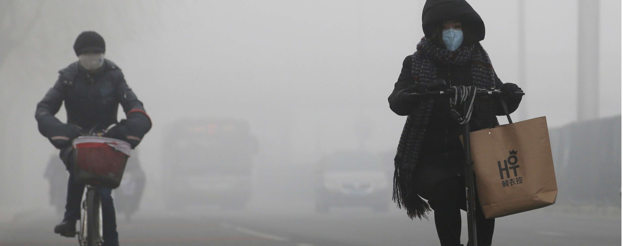 People ride amid the smog in Beijing. Photo: Reuters