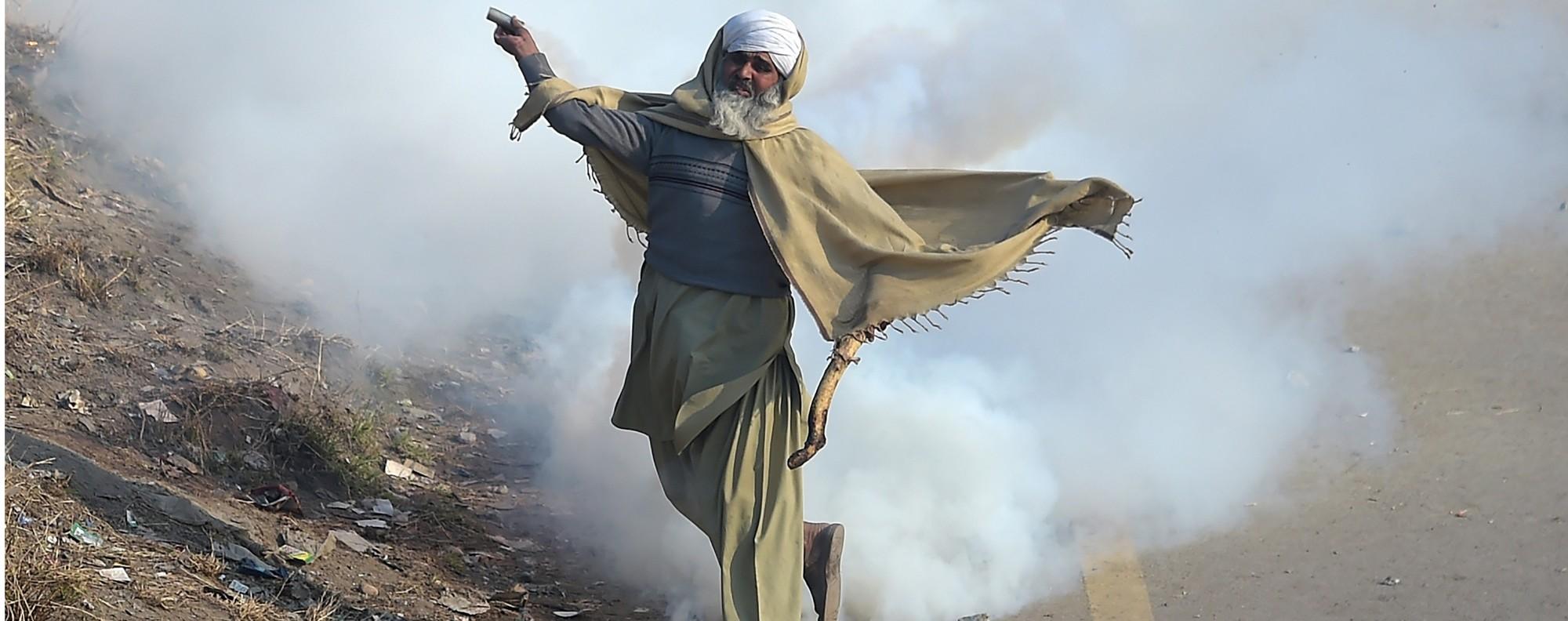 An Islamist throws a tear gas shell back at police. Photo: AFP