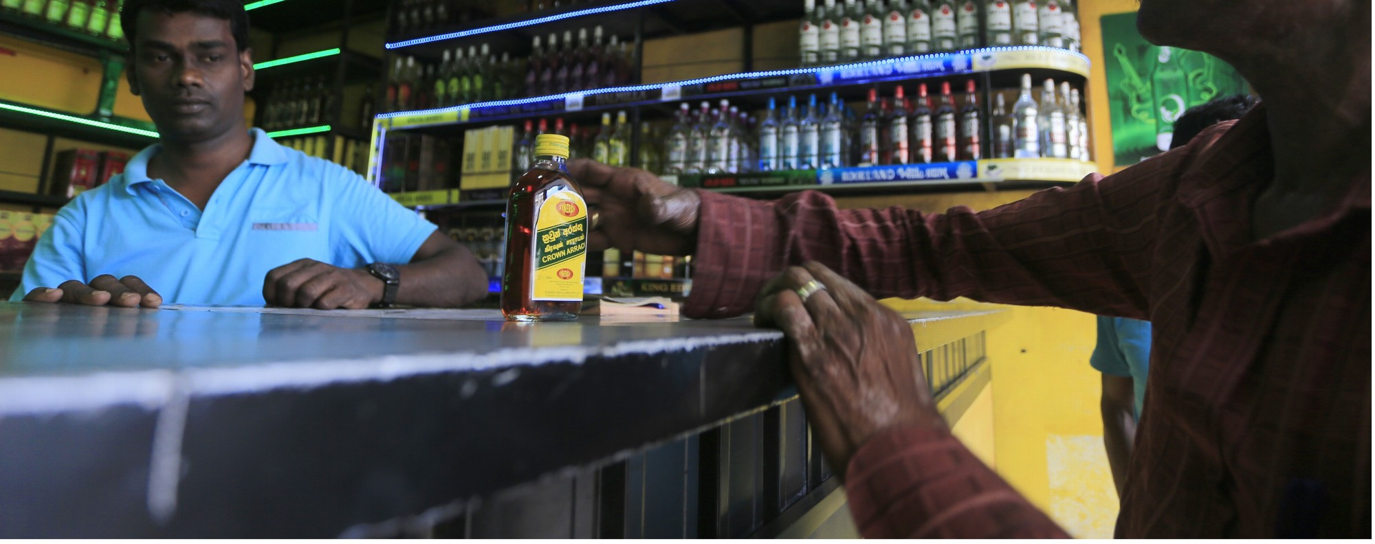 A Sri Lankan man buys liquor in Colombo. Photo: AP