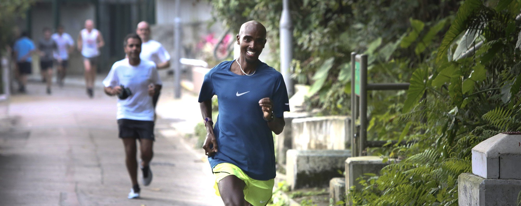 """Sir Mohamed Muktar Jama """"Mo"""" Farah jogs with supporters on Bowen Road in 2017. Bowen Road is a great option to keep training in the heat. Photo: Jonathan Wong"""