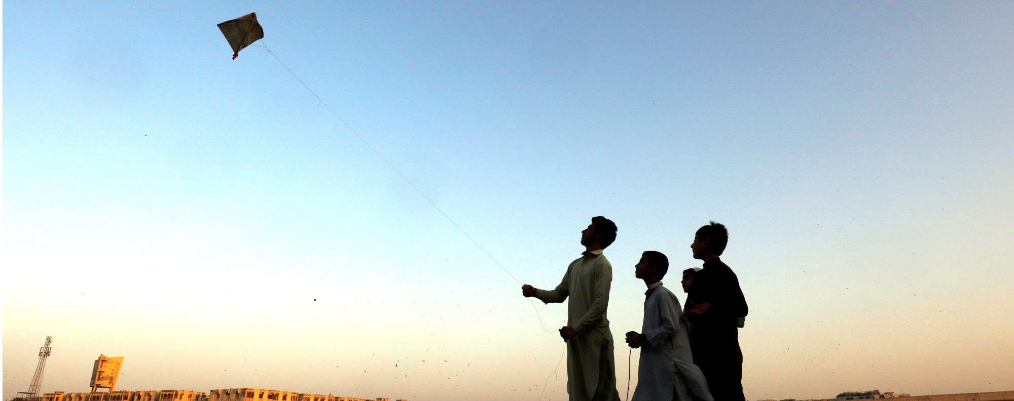Children fly a kite in Karachi, Pakistan. Photo: Reuters