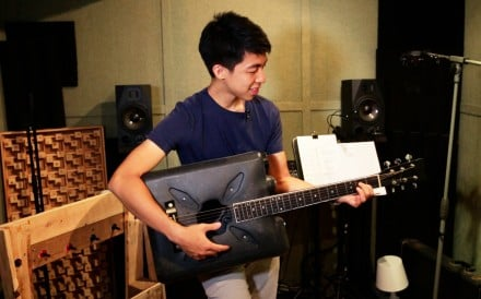 Kevin Cheung holds the guitar he made from a discarded plastic bottle.