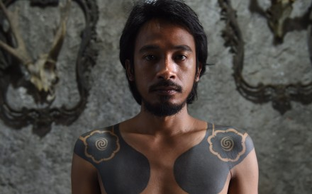 """To go with Indonesia culture tradition tattoo by Suryo Wibowo, with Sam Reeves in Jakarta In this photograph taken on October 14, 2015, Agung Prasetyo, an Indonesian care taker of Bau Tanah tattoo museum, displays his Dayak tribe motif tattoo in Jakarta. The practice known as """"hand-tapping"""" had almost faded out completely, as modernity overwhelmed Indonesia's tribes and younger generations eschewed their ancestors' ways, but tattoo artists have in recent years been driving a revival as more and more people seek to reconnect with the past. AFP PHOTO / ROMEO GACAD"""