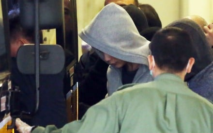 Zheng Yuzhou(in hood), 24-year-old from Chongqing, pleaded guilty to one count of remaining in Hong Kong without the authority of the director of immigration after having landed unlawfully, was escorted away from Tuen Mun Court. Zheng also admitted to driving without a driving license, driving an unlicensed vehicle and using a vehicle without a third party insurance. 12JAN15 SCMP/ K. Y. Cheng