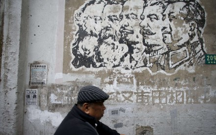 A resident rides an electric bicycle past an image painted during the Cultural Revolution, depicting German philosophers Karl Marx and Friedrich Engels, Soviet leaders Nikolai Lenin and Joseph Stalin, and Chinese leader Mao Zedong, on a wall at a soon-to-be-demolished housing area in Shanghai. Photo: Reuters
