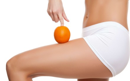 Woman with an orange showing a perfect skin without cellulitis.