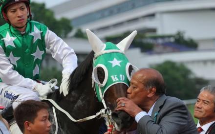 Kerm Din gives boom horse Pakistan Star a kiss, watched by jockey Matthew Chadwick and trainer Tony Cruz. Photo: Kenneth Chan