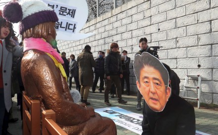 A South Korean protester wearing a mask of Japanese Prime Minister Shinzo Abe kneels in mock apology in front of the 'comfort women' statue outside the Japanese consulate in Busan. The statue symbolises the women who served as sex slaves for Japanese soldiers during the second world war. Photo: AFP