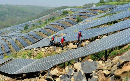 Chinese workers check solar panels last month on a hillside in a village in Chuzhou, Anhui province. China is now home to the world's fastest-growing renewable energy industry. Photo: AFP