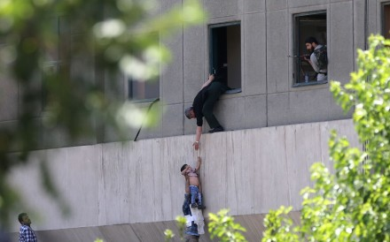 Iranian policemen evacuate a child from the parliament building in Tehran. Photo: AFP