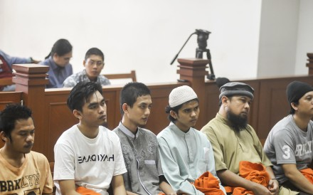 From L-R: Detained Indonesian militants Leonard Hutajulu, Hadi Gusti Yanda, Gigih Rahmat Dewa, Tarmiji, Trio Syafrido, and Eka Saputra attend a hearing at the East Jakarta court in Jakarta. Photo: AFP