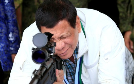 President Rodrigo Duterte at a Philippine air base, inspecting a rifle that came from China. Photo: Reuters