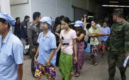 Myanmese workers are escorted by soldiers and police officers as they leave a shrimp shed after a raid conducted by Thailand's Department of Special Investigation in Samut Sakhon, Thailand. Photo: AP Photo