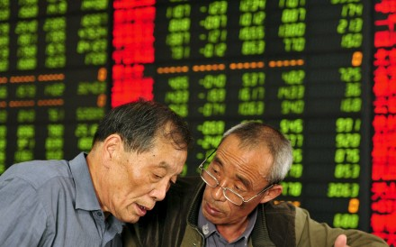 Investors talk as they look at a computer screen showing stock information at a brokerage house in Fuyang, Anhui province. Contrary to global conventions, China's financial markets depict gains and increases in red, while declines or reductions are displayed in green. Photo: Reuters