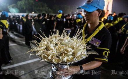 A volunteer holds dok mai chan used to mark the royal cremation ceremony. Two provincial governors have been transferred and denied new posts for shaming the ceremony. Photo: Bangkok Post