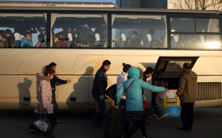 Migrant workers get on a long-distance bus to leave Beijing on November 24, after their factory was closed by the authorities in a crackdown on migrant worker communities. They will move to Changshu in Zhejiang, where the factory will be relocated. Photo: EPA-EFE