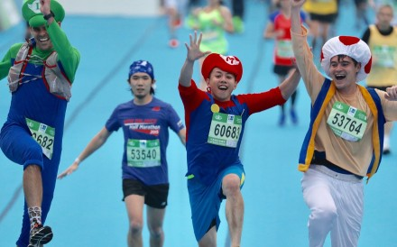 Runners dressed in Super Mario costumes cross the Hong Kong Marathon finish line at Victoria Park. Photo: Nora Tam
