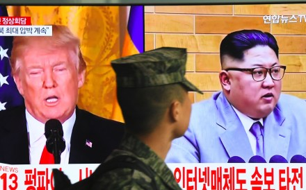 A South Korean soldier walks past a television screen showing pictures of US President Donald Trump and North Korean leader Kim Jong-un. The two heads of state are expected to meet in May. Photo: AFP