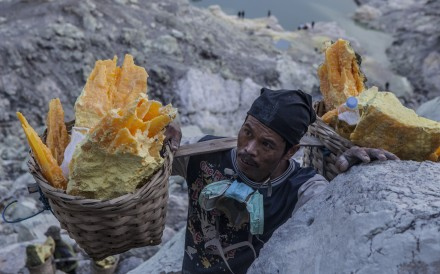 Miner carrying baskets of sulphur in Kawah Ijen, East Java, Indonesia. Photo: Agoes Rudianto