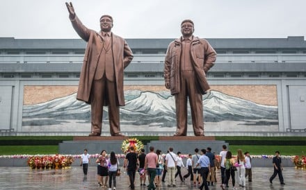 Locals and tourists in front of bronze statues of former North Korean leaders Kim Il-sung and Kim Jong-il at the Grand Monument on Mansu Hill in Pyongyang, North Korea.