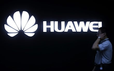 A man walks past a Huawei logo during a launch event for the Huawei Matebook in Beijing in 2016. Huawei is making bitcoin easier to access on its phones. Photo: AP