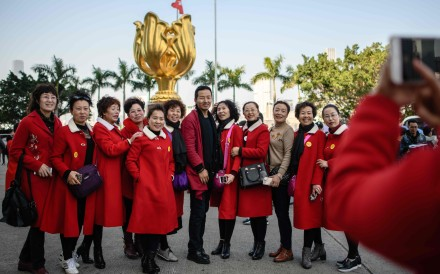Tourists from mainland China pose for photos in front of the Golden Bauhinia statue, a gift from the central government to Hong Kong in 1997 to celebrate the city's return to Chinese sovereignty, in Wan Chai in December 2017. Photo: AFP