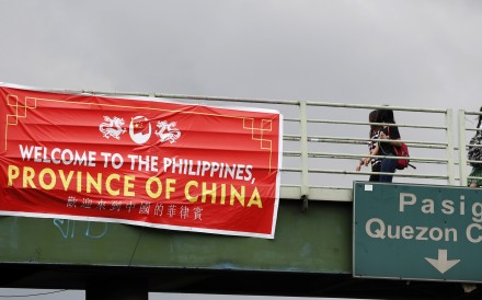 """A banner bearing the words """"Welcome to the Philippines, Province of China"""" hanging from a bridge in Taguig, south of Manila. Photo: EPA"""