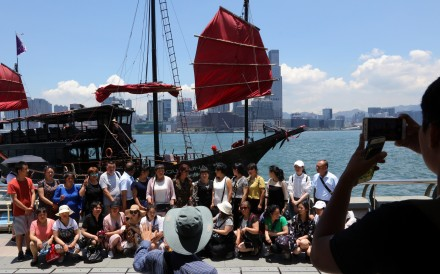 Tourists pose for a photo with a junk boat in the background at the Golden Bauhinia Square in Wan Chai. Photo: Felix Wong