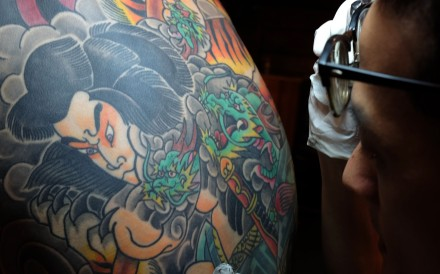Tattoo artist Bobo Chen inspects the inked back of his client Micky Peng. Photo: AFP