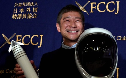 Yusaku Maezawa with a miniature rocket and space helmet. Photo: AFP