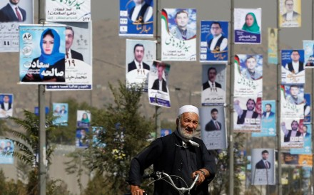 A man walks with his bicycle in front of election posters of parliamentary candidates during the first day of election campaign in Kabul, Afghanistan. Photo: Reuters