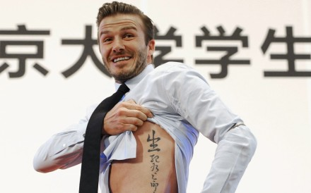 "David Beckham shows his tattoo during a visit to Beijing in 2013. The tattoo in Chinese characters reads, ""Life and death are determined by fate, rank and riches decreed by Heaven."" Photo: Reuters"