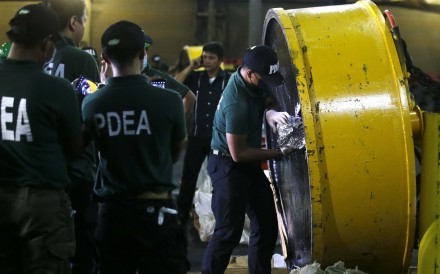 A member of the Philippine Drug Enforcement Agency opens a magnetic lifter containing packs of the drug shabu. Photo: AP
