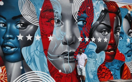 A man poses for a photo in front of a building covered with a mural by US artist Tristan Eaton in the Wynwood district during Art Basel in Miami, Florid. Photo: EPA-EFE