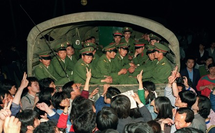 Pro-democracy demonstrators raise their fists and flash victory signs as they stop a military truck on its way to Tiananmen Square on May 20, 1989. Photo: AFP