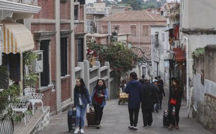 Tourists walk around Gulangyu, a popular pedestrian-only island off the coast of Xiamen. Photo: Roy Issa