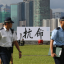 """Police officers walk past a billboard with the Chinese characters kang ming, or """"disobedience,"""" erected by the Occupy Central campaign, near Hong Kong's Central district on Aug. 31, 2014. Photo: Felix Wong"""