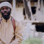 An IS fighter with an American accent tells people to use the USA's lax gun laws to acquire weapons for terrorism in this still from a recently released propaganda video.