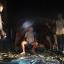 A park ranger stands guard over Italian-Thai Development Plc president Premchai Karnasuta, sitting, and the other suspects at their hunting camp in Thungyai Naresuan Wildlife Sanctuary in Kanchanaburi province. Photo: Piyarach Choncharoen/Bangkok Post