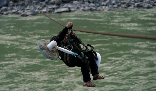 A villager carries an electric fan while zipping across the river.